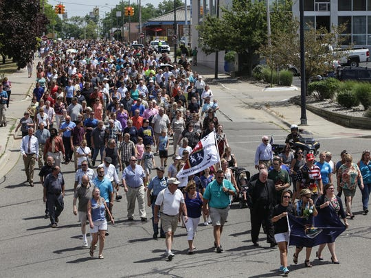 Hundreds of people march in memory of bailiffs Ron Kienzle and Joseph Zangaro from the Berrien County Courthouse in St. Joseph on Tuesday, July 12, 2016 to the Berrien County Law Enforcement Memorial after the bailiffs were shot and killed by inmate Larry Gordon on Monday at the courthouse.