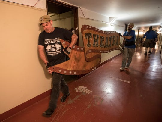 Matthew Pomroy, center, and Chris Herbon, right, help move signs out of storage for Theatre Bizarre set up at the Masonic Temple in downtown Detroit, Friday, October 6, 2017.