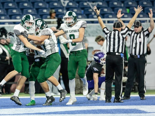 Grand Rapids West Catholic wide receiver Jack Schichtel (84), far left, celebrates with teammates after scoring a touchdown during the first half of the Division 5 state title game on Saturday, Nov. 25, 2017, at Ford Field.