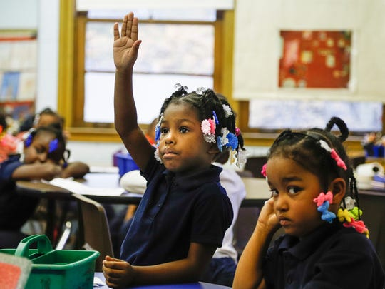 Iyonna Dinkins, raises her hands to answer a question in Karana Hale's art class at the Mann Elementary School in Detroit, Thursday, November 9, 2017. Next to Dinkins is Kamia McCullum.