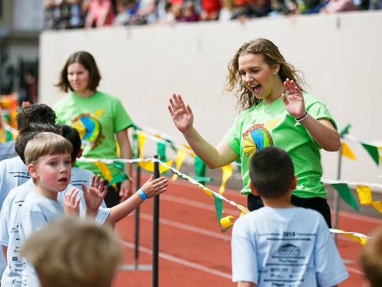 Volunteer Jordan Hagedorn high-fives runners after