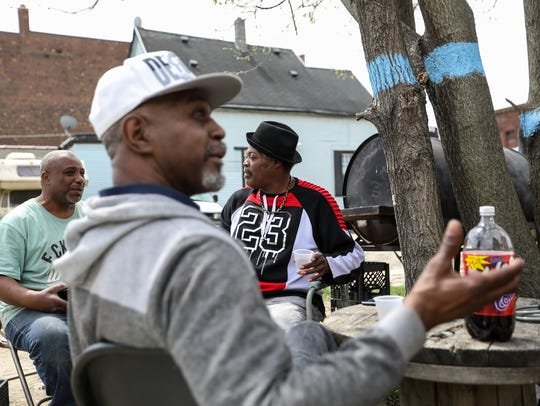 Andrew Johnson, 50, left, talks with his neighbor Leon