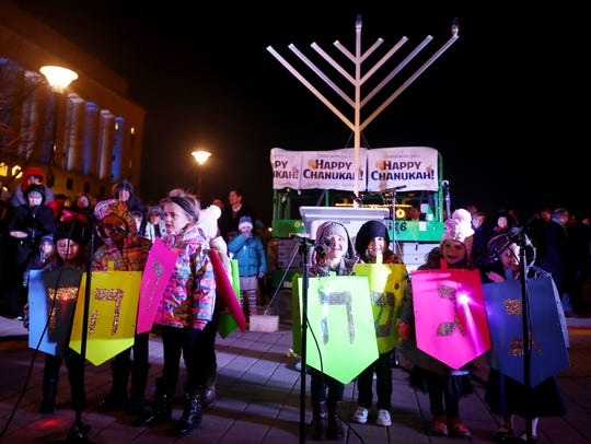 Students from The Revere Jewish Montessori School sing The Dreidel Song during the menorah lighting ceremony in honor of Hanukkah held in Public Square in Nashville on Tuesday December 12, 2017.
