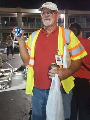 """A Florida Power & Light Co. lineman shows off the rock he was given that says """"Martin Co, Fl thanks you"""". Out-of-state lineman who came to help restore power after Hurricane Irma were treated to a potluck Saturday, Sept. 16, 2017 at Best Western on U.S. 1 in Stuart."""