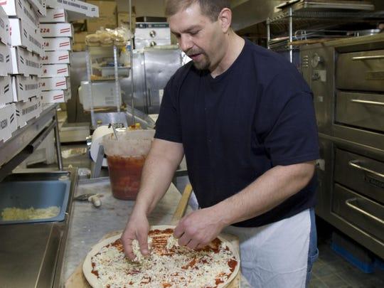 Joseph Hollish, owner of Joe Joe's pizza in Spring Lakes, makes a pie.