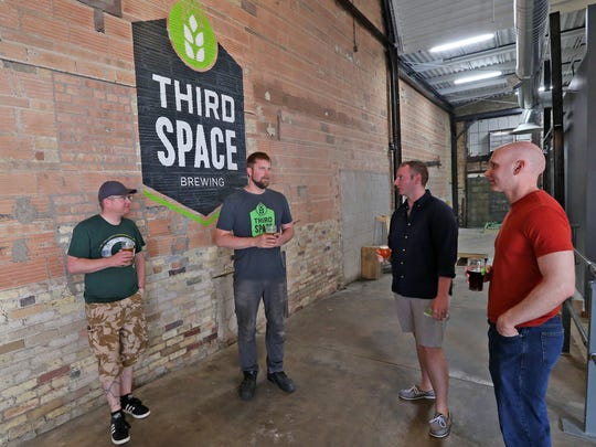 Kevin Wright (center) starts the tour at Third Space Brewing by talking about the relevance of the space they are housed in.