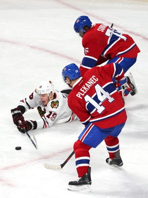 Chicago Blackhawks center Jonathan Toews (19) plays the puck against Montreal Canadiens center Tomas Plekanec (14) and defenseman P.K. Subban (76) during the third period at Bell Centre.
