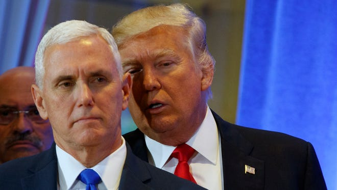 President-elect Donald Trump talks to Vice President-elect Mike Pence during a news conference Jan. 11 in the lobby of Trump Tower in New York.