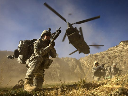 In this photograph, taken in 2008 at the height of U.S. troop deployment to Afghanistan, Army soldiers from 2-506 Infantry 101st Airborne Division and Afghan National Army soldiers take positions after running from the back of a UH-47 Chinook helicopter during the launch of Operation Shir Pacha into the Derezda Valley in the Spira mountains on the Afghan-Pakistan border.