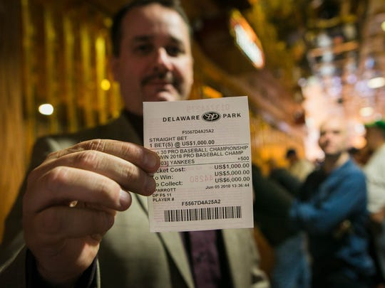 Tom Barton of Sound Beach, N.Y., holds up his $1,000 bet on the Yankees to win the World Series as he becomes the first person to place a bet. At 1:30 p.m. Tuesday, June 5, 2018, Delaware launched the country's first full-scale sports betting operation outside Nevada.