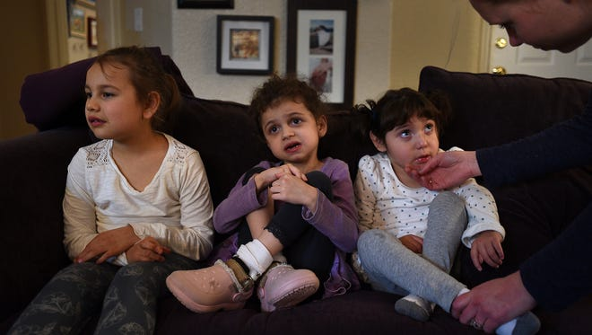 From left, Lila Barber, Scarlett Bertolino and Lennah Martinez sit together on a couch. A fundraiser for the three girls with cerebral palsy later this month will help pay for treatments.