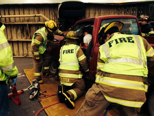 Firefighters use extrication tools to free and driver pinned inside a pick-up truck as part of the mass casualty incident training Sept. 13.