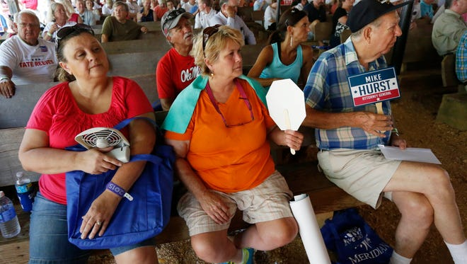 Fairgoers Patricia Speed, of Enterprise, left, and her friend Beverly Lee, center, and others try to cool down in the pavilion at Founders Square at the Neshoba County Fair in Philadelphia, Miss., Wednesday, July 29, 2015.