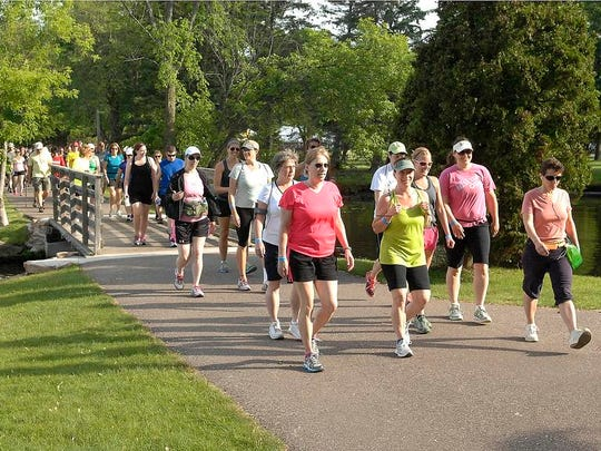 A long line of walkers doing the full marathon cross a small bridge in Pfiffner Park during Walk Wisconsin on the Green Circle Trail in Stevens Point.