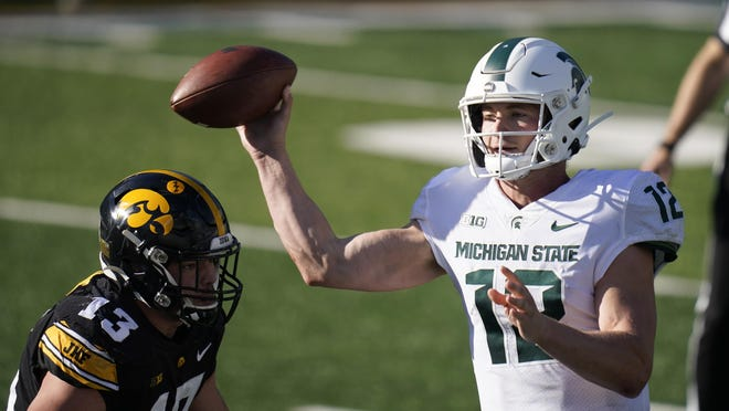 Michigan State quarterback Rocky Lombardi (12) throws a pass over Iowa defensive end Joe Evans (13) during the second half of an NCAA college football game, Saturday, Nov. 7, 2020, in Iowa City, Iowa. Iowa won 49-7.