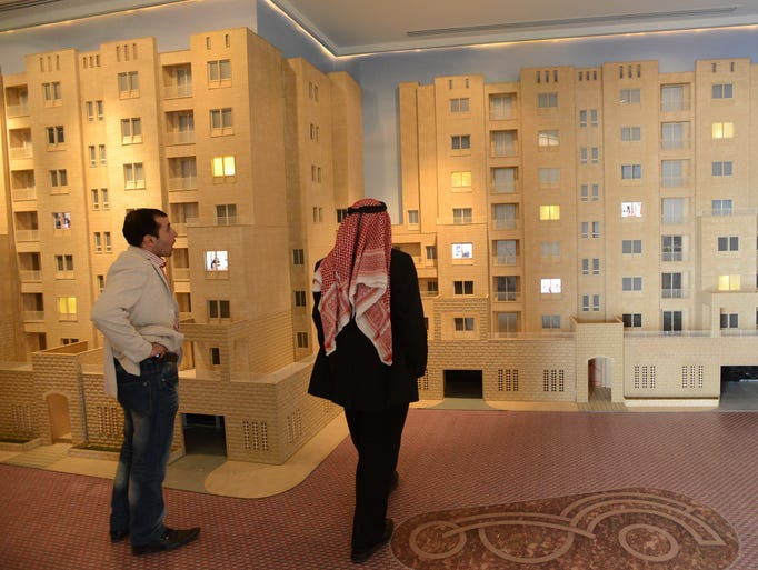 In the West Bank, a Palestinian looks at a model of Rawabi apartments in the visitor's center for the Palestinian building site and first planned community called Rawabi.
