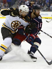Brandon Dubinsky, right, and the Bruins' Matt Grzelcyk chase a loose puck  Tuesday night.