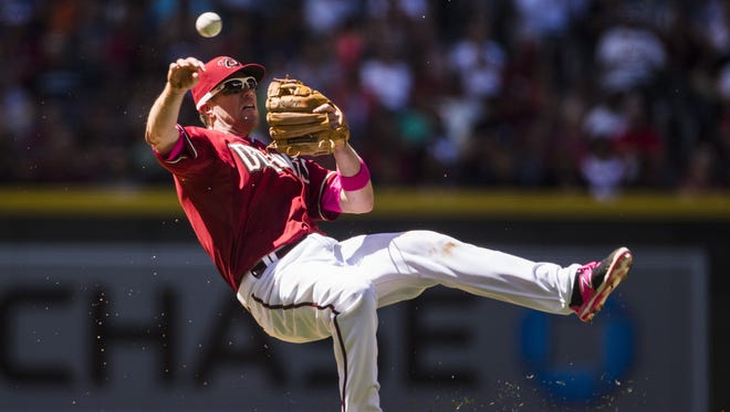 Diamondbacks' Aaron Hill makes a throw as he falls backward on May 10, 2015.