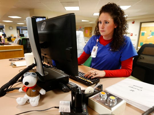 Brittney Null, a registered nurse at Mercy Hospital, works on discharging a patient in the pediatric intensive care unit on Wednesday, Aug. 31, 2016.