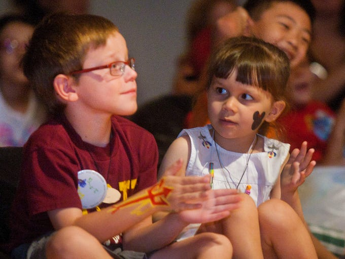 Ben and Lucy Lewandowsky clap after a performance by magician Jolly Roger at the ASU Art Museum.