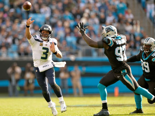 Russell Wilson throws under pressure from Mario Addison of the Carolina Panthers during the first half of their game at Bank of America Stadium on November 25, 2018 in Charlotte, North Carolina