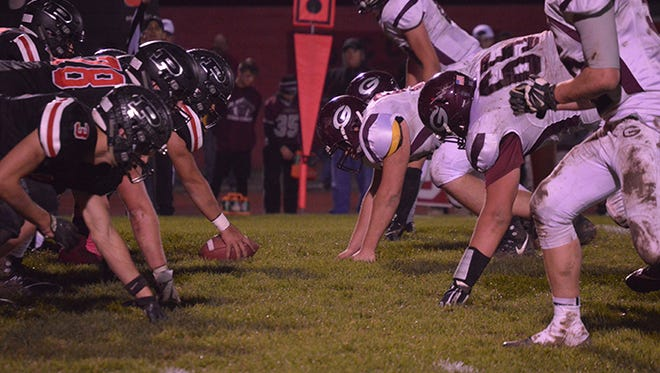 Pleasant, left, gets ready to snap the ball against Genoa in last week's 41-14 regional quarterfinal victory. The Spartans travel to Findlay to play Archbold in a Division V, Region 18 semifinal game Friday.