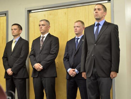 From left, newly sworn Burlington police officers David