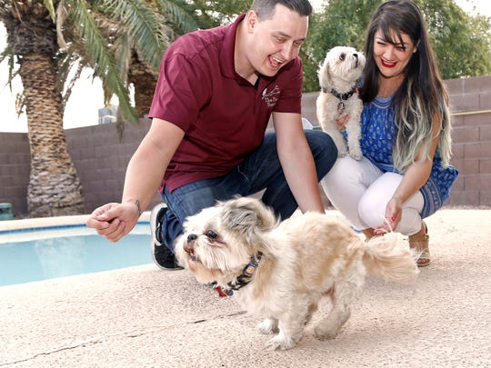 Stephanie Silva and Billy Horner sit out by the pool with their dogs Captain Jack (L) and Penny Lane at their new home in Mesa, Ariz. on April 6, 2018.