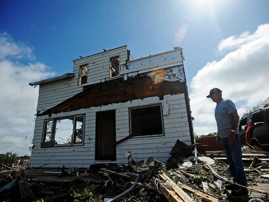 Ward Barber assesses the damage to what is left of his home and property on Thursday, June 19, 2014, after a tornado tore through the area on Wednesday in Wessington Springs, S.D.