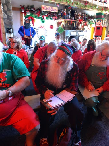 Lit by colorful lights in Santa's House, a roomful of Santas inluding Tom Cortemeglia of Nashville, TN, Jerry Julian of Colorado Springs and Don White of Fayetteville, GA,  left to right, take notes on being a better St. Nick at the Charles W. Howard Santa Claus School in Midland. Established in 1937, it is the longest continuously running Santa Claus School in the world.