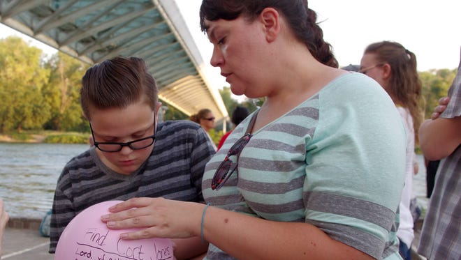 Jaden Briggs, 11, of Redding and his mother, Jessica Briggs, sign a balloon they released Saturday in memory of Cort Jones of Redding, who went missing in August 2012. Jessica Briggs is Jones' aunt.