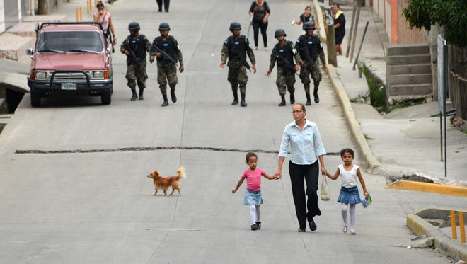 "A woman takes two girls by the hand as she walks along a street guarded by military police personnel, in the neighborhood of Flor del Campo, on the outskirts of Tegucigalpa on July 13, 2014. Honduran President Juan Orlando Hernandez ordered the creation of 113 strongly guarded ""playgrounds"" across the country during weekends, for children to play safely and people circulate without fear as well as to promote a peaceful coexistence in areas where violence is an everyday occurrence."