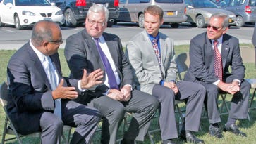 Trip Tripathy, CEO of the DeMet's Candy Co., left, chats before a news conference begins Thursday in Big Flats with, from left, state Sen. Tom O'Mara, state Assemblyman Chris Friend and Chemung County Executive Tom Santulli.