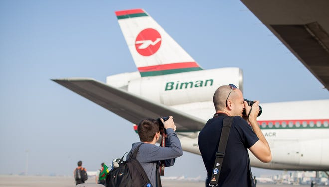 Aviation enthusiasts snap photos of a Biman Bangladesh Airlines DC-10 before the plane makes its final passenger flight.