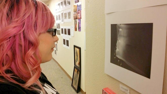 Courtesy Photo Kat Quarrell, a sophomore at Western New Mexico University, takes in one of the many art works on exhibit during the Expressions in Art show held this past Friday on the Silver City campus.
