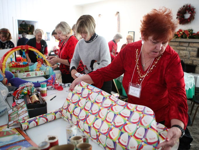 Crestwood Civic Club member Sharon Clark, right, works with other members as they finish wrapping presents and making gift and food baskets for outreach families and the Teddy Bear giving tree. Nov. 13, 2013
