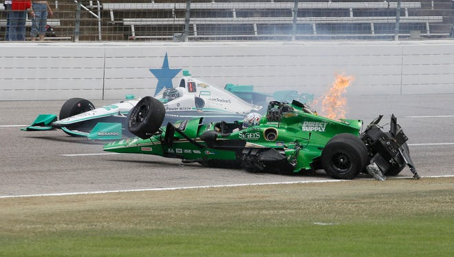 Josef Newgarden's car rolls to the upright position after being involved in a wreck with Conor Daly during an IndyCar auto race at Texas Motor Speedway, Sunday, June 12, 2016, in Fort Worth, Texas. (AP Photo/Tim Sharp)