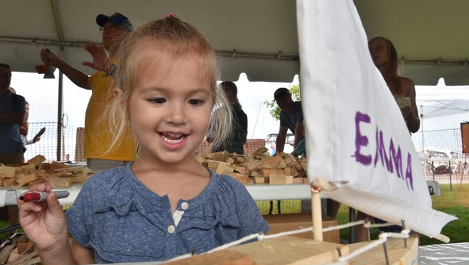 Emma Hilde, 3, Sycamore, Ill., admires the artistry of her handmade boat in a workshop last year hosted by the Sister Bay Lions.
