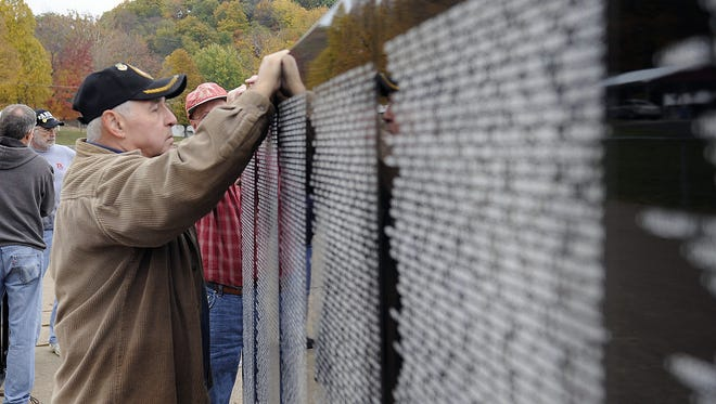 Larry Smith, Air Force Veteran, holds a panel of the Vietnam Traveling Memorial Wall in Lancaster. The wall is traveling to Bellevue Wednesday and will be displayed at Central Park through next weekend during Bellevue Community Days event.