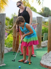 Eliana Valencia, 7, putts while her mother, Jessica