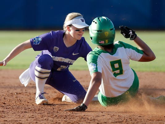 Washington's Sis Bates (22) tags out Oregon's Shannon Rhodes (9) at second base during the fourth inning of anNCAA Women's College World Series softball game in Oklahoma City, Thursday, June 1, 2017. (Bryan TerryThe Oklahoman via AP)