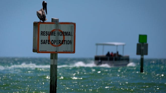 A pelican sits atop a boating sign indicating a return to normal boating operations near Wiggins Pass on Thursday, June 23, 2016, in North Naples.