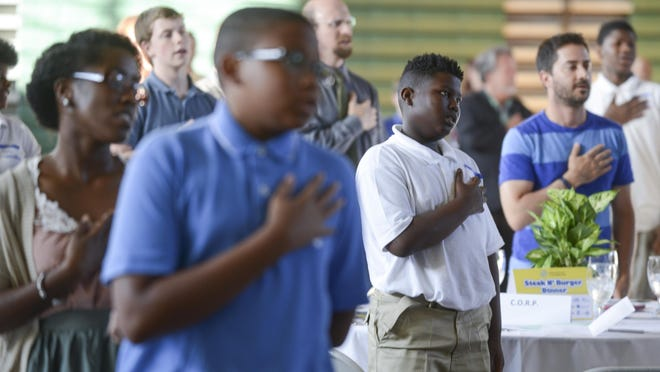 People recite the Pledge of Allegiance at the annual Boys & Girls Club Steak and Burger Dinner fundraiser.
