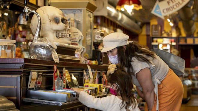 Carolyn Brown and her daughter Willow, 2, shop at Big Top Candy Shop in Austin on Oct. 22. Retail sales growth in Texas slowed this month, according to the Dallas Fed.