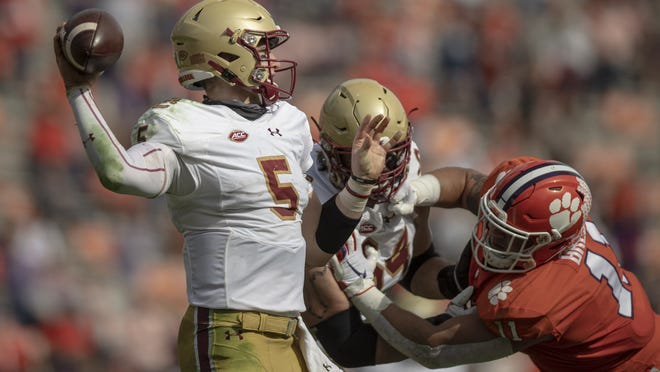 Boston College quarterback Phil Jurkovec (left) passes the ball near Clemson defensive lineman Bryan Bresee (right) during the first quarter of the game at Memorial Stadium.