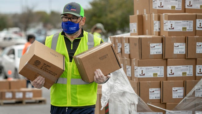Kyle City Councilman Robert Rizo, a volunteer with the Central Texas Food Bank, works at a drive-through food distribution at Lehman High School in Kyle in November. Central Texas Food Bank was one of the 111 recipients of the final grants of the All Together ATX fund.