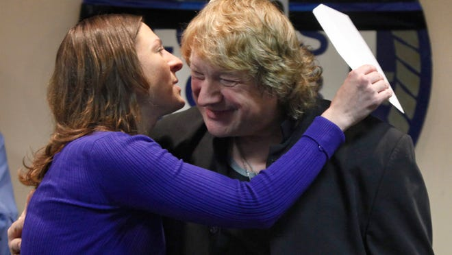 Amy Pierson, widow of slain Rochester Police Officer Daryl Pierson, hugs local musician Lou Gramm after he presented her with a check for $15,000 at the Locust Club on Tuesday morning. The money was raised at a benefit concert held at the Main Street Armory on December 6, 2014. Gramm, former lead singer of Foreigner, performed at the concert.