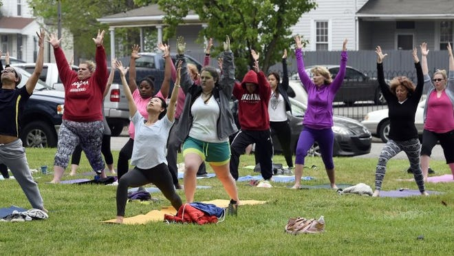 JASON CLARK / COURIER & PRESS Local residents take part in an outdoor yoga session during the Earth Day Franklin Street Bazaar earlier this year on the lawn of the West Side Library Park.