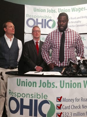 (From left:) Woody Taft, William Foster and NFL player Frostee Rucker talk with reporters before signing an agreement to allow workers to unionize at their marijuana farms that would be set up should voters approve a proposed constitutional amendment offered by the private group ResponsibleOhio.