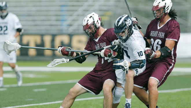 Pittsford's Matt Malone is sandwiched between Orchard Park's Billy Myers and Louis Nephew while trying to get to the ball in the fourth quarter on May 30, 2015.